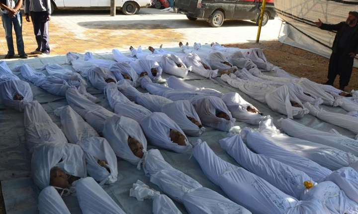 Activisti sirieni inspectînd corpurile unor civili ucisi în 2014 în urma unui atac chimic
