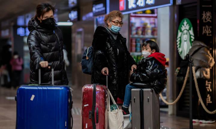 Calatori poarta masti de protectie într-o gara din Beijing, 24 ianuarie 2020.
