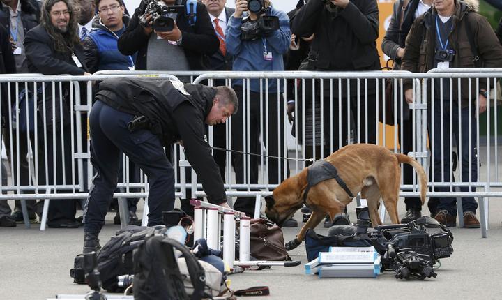 Un poliţist inspectează echipamentul jurnalistic la COP21 (Foto: Reuters/Jacky Naegelen)