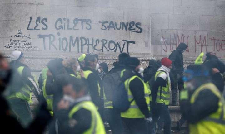 """""""Vestele galbene vor triumfa"""" slogan scris pe Arcul de Triumf de la Paris, 1 decembrie 2018."""