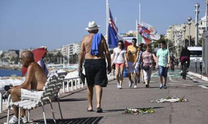 Pe 17 iulie 2016, oamenii se plimbau pe Promenade des Anglais printre florile asezate ca omagiu victimelor atacului din 14 iulie de la Nisa