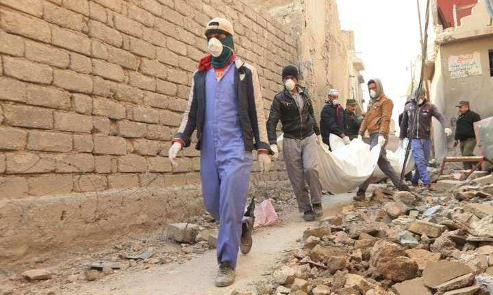 Locuitori din Mosul transportà cadavre gàsite în ruinele orasului vechi, 17 ianuarie 2018