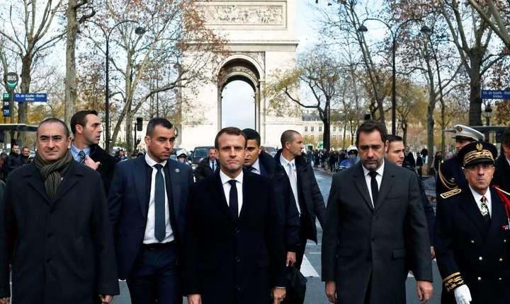 Preşedintele Emmanuel Macron (centru) şi ministrul de interne Christophe Castaner pe bulevardul Champs-Elysées