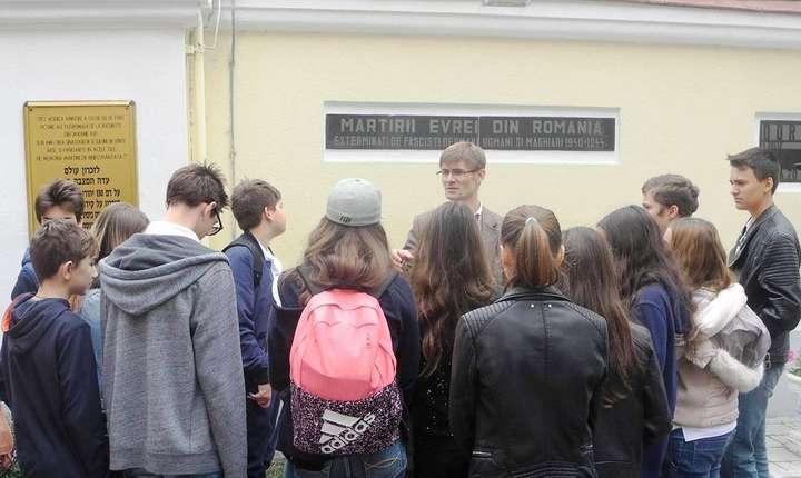 Profesorul Marcel Bartic și elevii săi la un monument al victimelor Holocaustului