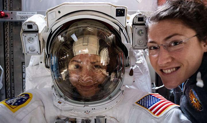Jessica Meir (în costum de astronaut) și Christina Koch pozează pentru istorie (Sursa foto: site NASA)