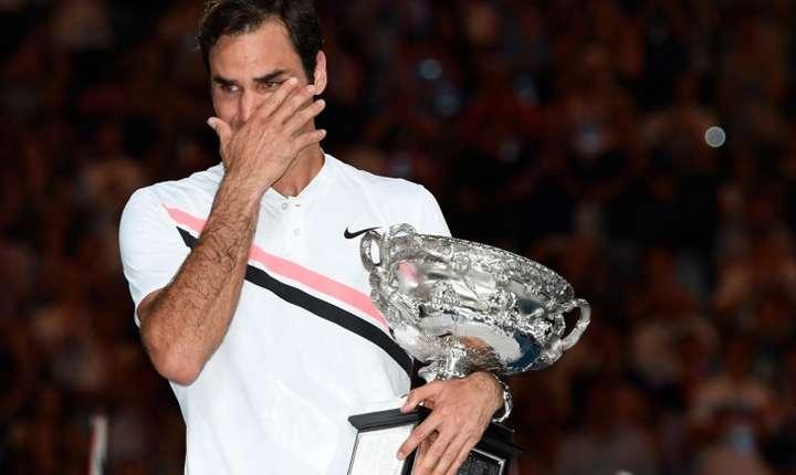 Roger Federer plânge, în timp ce ţine în braţe trofeul de la Australian Open (Foto: AFP/Saeed Khan)
