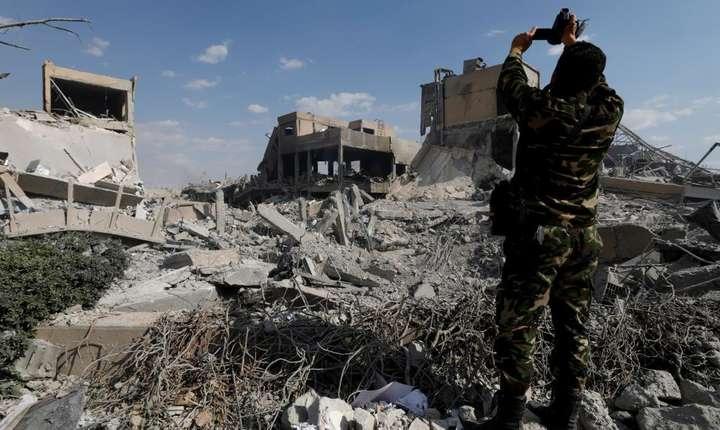 Un militar sirian filmeazà ruinele unui centru de cercetàri din periferia Damascului, bombardat pe 14 aprilie de coalitia tripartità