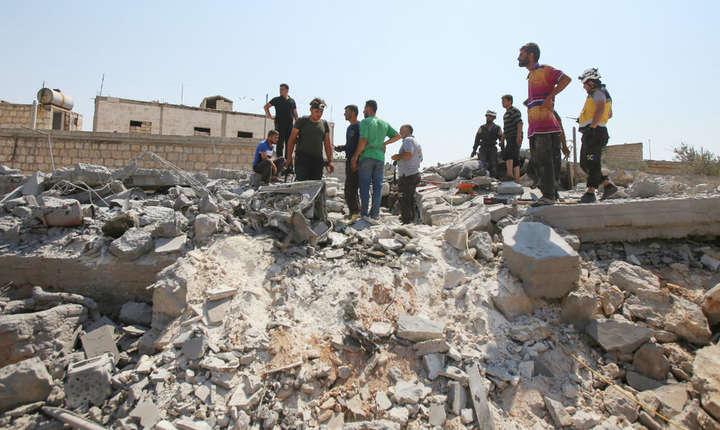 Sirieni observa pagubele produse în urma unui atac aerian asupra localitatii Deïr Charki, în provincid Idleb, 17 august 2019.