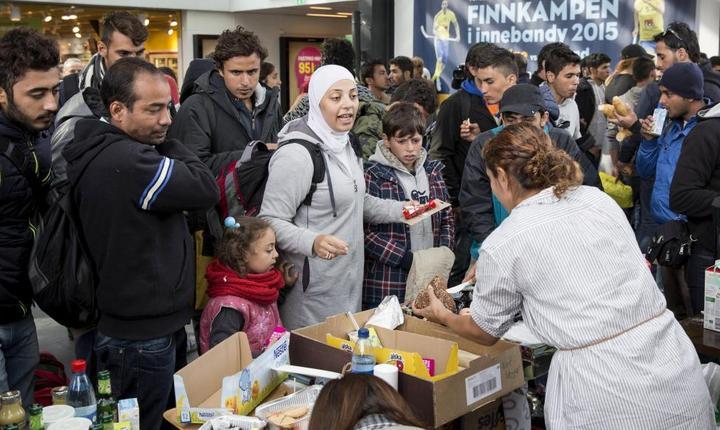 Voluntari distribuie hranà si apà refugiatilor care ajung în gara suedezà de la Malmö, septembrie 2015