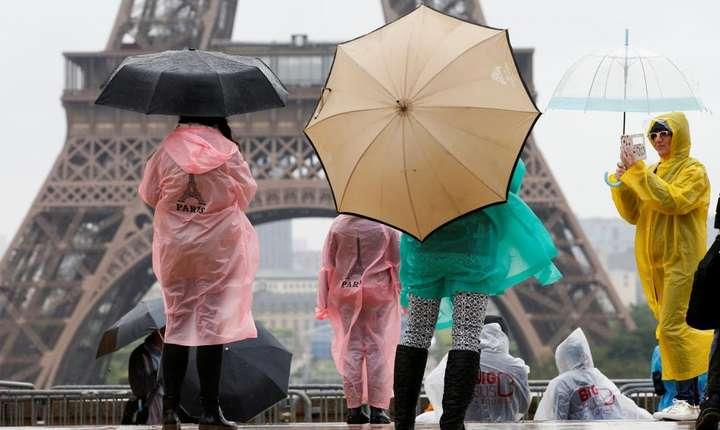 Turisti în fata Turnului Eiffel care a fost construit pentru a zecea expozitie universala ce a avut loc în 1889 la Paris