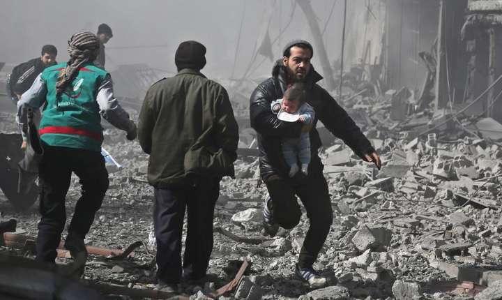 Un barbat fuge, cu un copil în bratele sale, din calea bombardamentelor regimului sirian ce au loc în Ghouta orientala, nu departe de Damasc, 19 februarie 2018