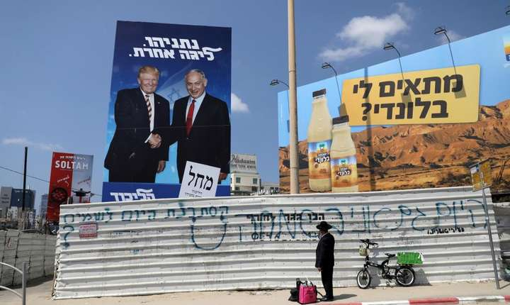 Un ultra-ortodox priveste afisul partidului Likud în care premierul Benjamin Netanyahu da mâna cu Donald Trump.