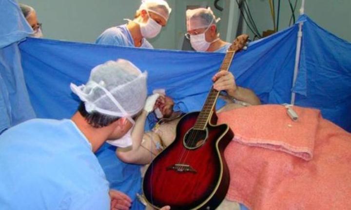 Brazilianul Anthony Kulkamp Dias cântă la chitară, în timp ce este operat pe creier