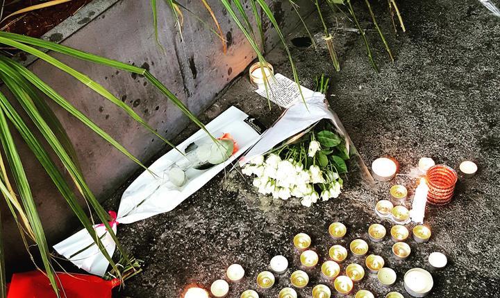 Lumânàri si flori în fata cafenelei La Bell Equipe unde au fost ucise 21 de persoane