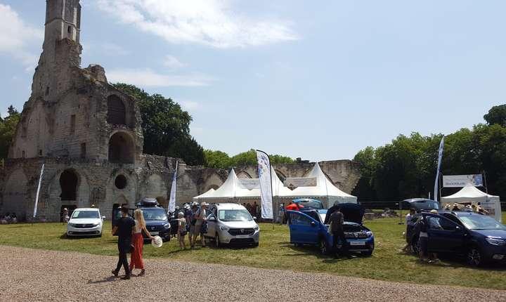 Ruinele abatiei cisterciene înconjurate de masini, produse si fani Dacia