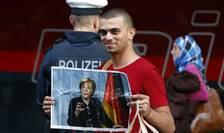 Migrant arborînd portretul doamnei Merkel pe data de 5 septembrie 2015 în gara la München.