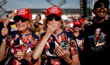 """Suporteri ai președintelui Donald Trump cu șepci roșii inscripționate cu """"Keep America Great"""" si tricouri imprimate cu portretul lui Trump"""