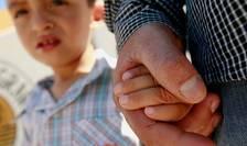Un migrant din Salvador împreuna cu fiul sau, Centrul de refugiati de la Ciudad Juarez, Mexic, 19 iunie 2018.