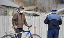 Un polițist discută cu un localnic din Țăndărei, localitate aflată în carantină în aprilie 2020 (Sursa: MEDIAFAX FOTO/Andreea Alexandru)