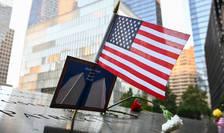 Drapelul american si o fotografie a turnurilor gemene a World Trade Center pot fi observate deasupra unui nume a victimelor atacurilor de la 11 septembrie 2001, la memorialul din New York.