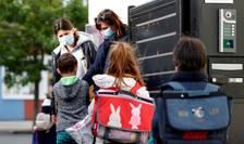 Copii se spalà pe mâini înainte de a intra într-o scoalà de lângà Nantes, 12 mai 2020