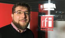 Dragoș Apostu in studioul de inregistrari, langa un panou cu logo-ul RFI Romania