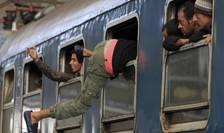 Un imigrant intră pe geam într-un tren din gara Keleti din Budapesta (Foto: Reuters/Bernadett Szabo)