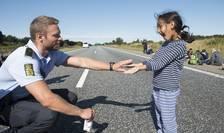 Un poliţist danez se joacă împreună cu o fetiţă refugiată (Foto: Reuters/Claus Fisker/Scanpix)