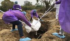 Membrii unei familii înmormântează o rudă decedată din cauza Covid 19