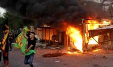 Manifestant siit fluturà un drapel în fata sediului televiziunii Dijlah din Bagdad, incendiat dupà ce a difuzat muzicà într-o zi sacrà pentru siiti, august 2020.