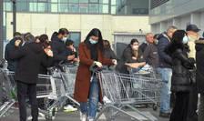 Italieni poarta o masca de protectie la intrarea într-un supermarket din Casalpusterlengo, unul din orasele plasate în carantina, 23 februarie 2020.