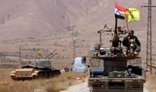 Drapelul sirian şi steagul mişcării Hezbollah flutură pe un vehicul militar sirian (Foto: Reuters/Omar Sanadiki)