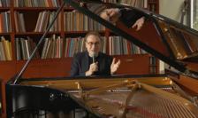 Jean-François Zygel in spatele pianului cu un microfon in mana