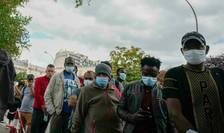 Migranti stau la coadà la Paris ca sà se vaccineze într-un centru pus la dispozitie de ONG-ul Médecins sans frontières. 29 iulie 2021.