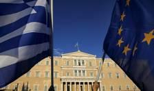 Protestatari ţin steagul Greciei şi pe cel al UE, în faţa Parlamentului din Atena (Foto: Reuters/Yannis Behrakis)