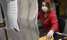 O casieră dotată cu o mască lucrează în spatele unei folii de plastic pentru a se proteja de coronavirus într-un magazin din Strasbourg, 19 martie 2020.
