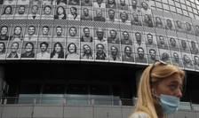 O femeie poarta o masca traversând în fata Operei Bastille din Paris, cladire pe care pot fi vazute portretele îngrijitorilor ce s-au ocupat de pacientii cu Covid-19 în timpul pandemiei, 10 iulie 2020.