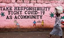 O femeie trece prin fata unui zid pictat ca un apel la responsabilitate din partea fiecaruia, în lupta împotriva Covid-19, Nairobi, Kenya.