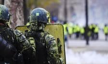 Poliţişti stropiţi cu vopsea galbenă, pe Bulevardul Champs-Elysées, în contextul unei manifestaţii, 1 decembrie 2018