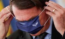 Presedintele brazilian este observat în timp ce încearca sa îsi aranjeze masca sanitara, Brazilia, 22 martie 2021.