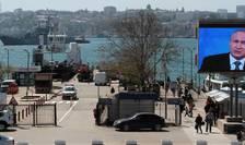 Pe un ecran gigantic montat în portul Sevastopol se retransmite discursul lui Vladimir Putin, aprilie 2016