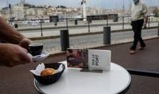 Un barbat ce poarta o masca sanitara trece pe lânga o terasa din portul Marseille, înca deschisa în aceste zile. De sâmbata, 26 septembrie, barurile si restaurantele sunt obligate sa ramâna închise.