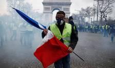 Un protestatar din miscarea Vestele galbene, cu un drapel francez în mâna, pe Champs Elysées, în apropiere de Arcul de Triumf din Paris, 8 decembrie 2018.