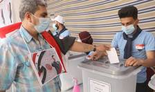 Un sirian rezident în Liban, poarta la gât portretul lui Bachar al-Assad în timp ce voteaza în cadrul alegerilor prezidentiale, 20 mai 2021, la un birou de vot amenajat în Ambasada Siriei din Beirut.