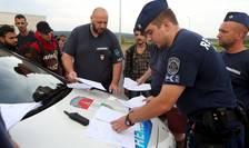 Poliţişti din Ungaria controlează actele unor imigranţi (Foto: Reuters/Srdjan Zivulovic)