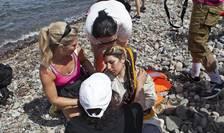 Voluntari ajuta o refugiata siriana ajunsa pe insula greceasca Lesbos, 7 septembrie 2015
