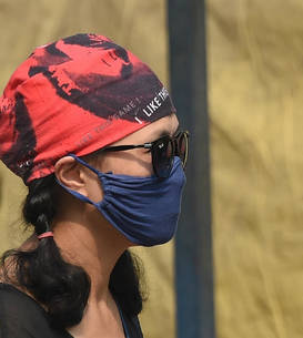 O femeie poartă o mască anti-poluare la New Delhi, 2018 (Sursa foto: AFP/Prakash Singh via France24)