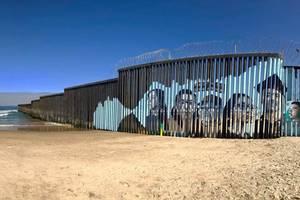 Fresca murala - portrete ale unor migranti pe bariera metalica ce separa Statele Unite de Mexic.