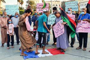În Tripoli, manifestanti calcă în picioare drapelul francez în cadrul unui protest împotriva declaratiilor făcute de președintele francez la adresa caricaturilor cu profetul Mahomed, Libia, 25 octombrie 2020.
