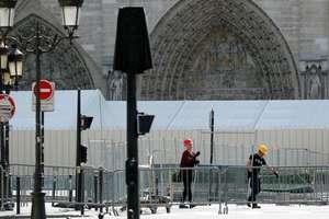 Lucratori instaleaza bariere în fata catedralei Notre Dame din Paris, 13 august, pentru îndepartarea prafului ce contine plumb.